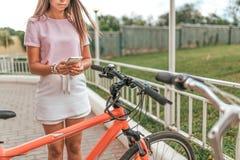 Девушка держит руку мобильного телефона, фотоснимки паркуя велосипед В применении города лета онлайн, столб интернета в социально стоковые фотографии rf
