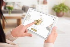 Девушка добавляет ботинки к корзине с онлайн приложением стоковая фотография