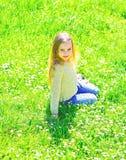Девушка сидит на траве на grassplot, зеленой предпосылке Ребенок наслаждается погодой весны солнечной пока сидящ на луге расцвет стоковые изображения