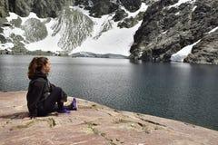 Девушка сидя на утесе восхищает горы и ледники которые падают на озеро стоковое изображение rf
