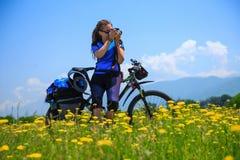 Девушка с велосипедом снимает фото на зацветенном поле стоковое фото