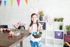 Девушка с красочными пасхальными яйцами показывая довольство стоковое изображение rf