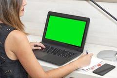 Девушка работая с тетрадью на столе зеленый цвет chroma ключевой стоковые изображения rf