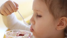 Девушка ребенка есть десерт в кафе Портрет младенца который ест мороженое closeup акции видеоматериалы