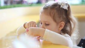 Девушка ребенка есть десерт в кафе Портрет младенца который ест мороженое closeup видеоматериал