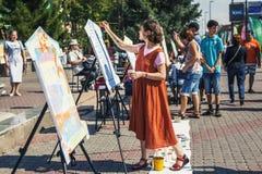 Девушка рисует на листе бумаги, мольберты и краска на улице Миры и любое может нарисовать wh стоковая фотография rf