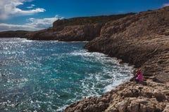 Девушка Llittle стоящ и смотрящ море на красивом береге моря в Кипре Красивый берег моря в Кипре Взгляд стоковое фото