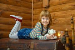 Девушка Masha лежит на старом комоде стоковые изображения rf