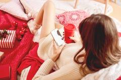 Девушка одела связанное платье и связанные лож носков на красно-белых одеялах и подушках и держит мобильный телефон и красную чаш стоковые фото