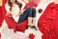 Девушка одетая в белом связанном свитере, джинсах и связанных лож носков на красно-белых одеялах и подушках с красной чашкой  стоковые изображения