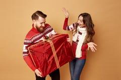Девушка surprisly смотрит парня держа огромный подарок Они оба одеты в красных и белых свитерах с оленями стоковое фото