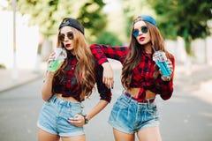 Девушки улицы лета, 2 девушки на улице, сестры, 2 красивых девушки идут вокруг городка модно и стильно стоковые фото