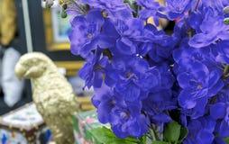 Декоративные голубые цветки на предпосылке золотого figurine попугая стоковое фото rf
