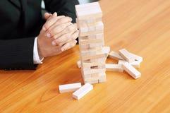 Деловая игра Jenga, выполнение дела строя конюшню основания дела основания дела неудачную и неустойчивое основание дела стоковая фотография rf