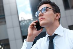 Деловые сообщества Бизнесмен в eyeglasses идя на улицу города вызывая на смартфоне смотря вверх задумчивый стоковые изображения