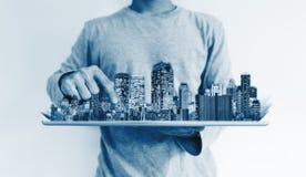 Дело недвижимости и вклад, умная технология строительства человек используя цифровой планшет с hologram зданий стоковое изображение