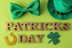 День ` s StPatrick праздник Зеленая шляпа лепрекона, клевера, связи бабочки, подковы и текста на яркой ой-зелен предпосылке top стоковое изображение