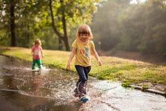 Дети скача в лужицу воды стоковые фотографии rf
