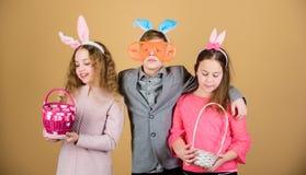 Дети со звероловством маленькой корзины готовым для пасхальных яя Друзья имея потеху совместно на день пасхи Подготавливайте для  стоковое изображение