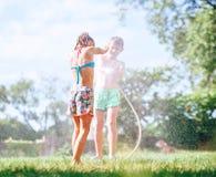 2 дет играя на саде, льют один другого от шланга, делают дождь стоковое изображение rf
