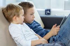 2 дет используя планшет сенсорного экрана дома, современная технология образования Братья с планшетом в светлой комнате стоковое изображение