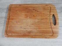 Деревянная доска для резать еду на таблице в кухне стоковые фотографии rf