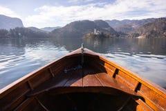 Деревянная шлюпка на кровоточенном озере, конец ренты шлюпки смотря на к острову кровоточенному озером с туристом космоса экземпл стоковые изображения