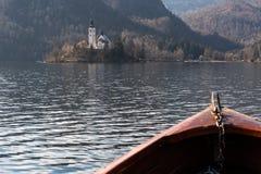 Деревянная шлюпка ренты, конец шлюпки смотря на к острову кровоточенному озером, фокусу на острове Bled - известном туристском на стоковое фото rf
