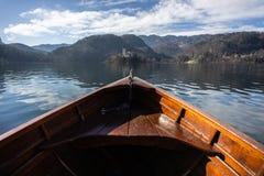 Деревянная шлюпка ренты, конец шлюпки смотря на к острову кровоточенному озером - космос экземпляра и фокус на острове Bled, тури стоковое фото