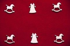 Деревянные игрушки на красной предпосылке Лошади и колоколы игрушки деревянные стоковые изображения rf