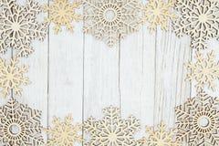 Деревянные снежинки на выдержанной текстурированной побелкой предпосылке древесины стоковое фото rf