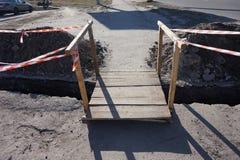 Деревянный мост через канаву выкопанную для того чтобы отремонтировать сообщения стоковые изображения
