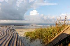 Деревянный променад, море, трава дюны и драматическое небо стоковые изображения