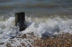 Деревянный столб встречает волны стоковое изображение