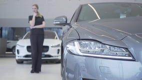 Диаграмма женщины Blurred усмехаясь в черном положении носки в мотор-шоу смотря вокруг Фара современного серебряного автомобиля в видеоматериал