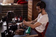Дизайнер ботинка создавая проект стоковое фото rf