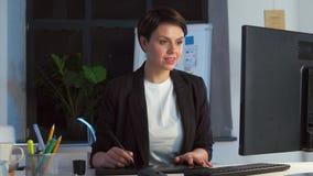 Дизайнер с компьютером и таблеткой ручки на офисе видеоматериал