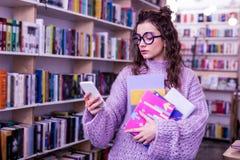 Длинн-с волосами внимательная женщина проверяя ее сообщения пока носящ книги стоковое фото