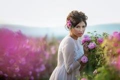 Длинное платье свадьбы, красивый стиль причесок и поле цветков стоковое изображение