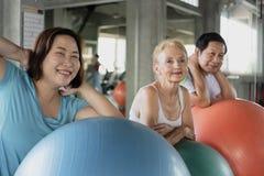 Друг группы старшия на спортзале йоги представляя полагаться на ее шарике усмехаясь и счастливого пожилой здоровый образ жизни стоковые изображения rf