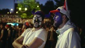 Друзья вентиляторы красят на стороне футбол дозора против ночи вентилятора толпы фона видеоматериал