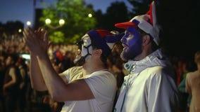 Друзья с краской на стороне в победе наслаждения socer или футбольного матча медленного mo сток-видео