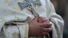 Рπιό riest κρατά έναν σταυρό στα χέρια του Η ιεροτελεστία εκκλησιών Ο σταυρός εκκλησιών στα χέρια ιερέων ` s φιλμ μικρού μήκους