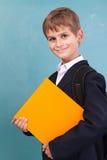 Ð ¡犹特人男小学生拿着橙色书 免版税库存图片