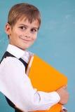 Ð ¡犹特人男小学生拿着橙色书 库存照片