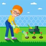Ð- Frau, die die Blumen im Garten im Frühjahr wässert Lizenzfreies Stockfoto