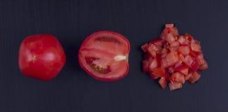 Ð-¡ hüpfte Tomaten auf einem schwarzen Hintergrund Stockfotos
