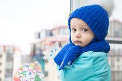 Ð ¡ hild在调查窗口的家在冷的冬日等待的圣诞节期间 免版税库存照片