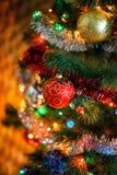 Ð-¡ hristmas klumpa ihop sig på julgranen med den ljusa girlanden Arkivbilder