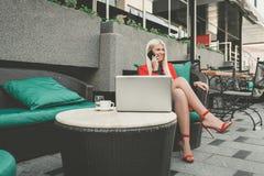 Довольно молодая женщина имея разговор сотового телефона пока сидящ передний открытый ноутбук стоковое изображение